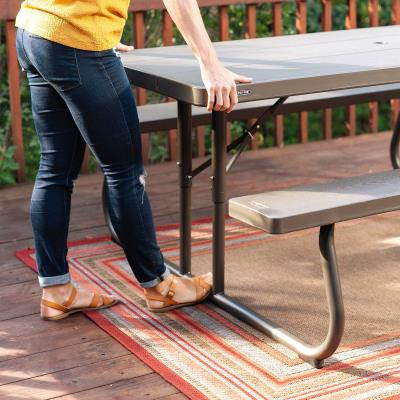 Lifetime 6-Foot Picnic Table - The 72 in. x 30 in. high-density polyethylene tabletop is stain resistant, easy to clean, and folds flat for storage. This model comes in brown with a wood grain texture and a bronze 1-5/8 in. round folding frame that includes an umbrella hole and cap. Single box packaging. 2-year limited warranty. photo